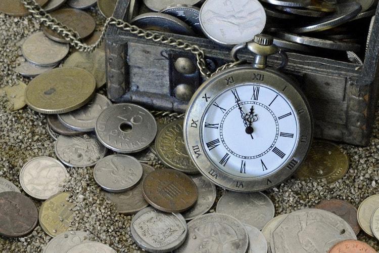 Geldmünzen und Taschenuhr